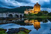 Since restoration in the early 1900s, a footbridge connects the island of Donan to the mainland. Eilean Donan Castle looks spectacular when spotlit at twilight, in Kintail National Scenic Area, Scotland, United Kingdom, Europe. This picturesque island stronghold was first built in the 1200s in the western Highlands where three sea lochs meet (Loch Duich, Loch Long, and Loch Alsh) at the village of Dornie. The island is named after Donnán of Eigg, a Celtic saint martyred in 617. The castle became a stronghold of the Clan Mackenzie and their allies Clan Macrae. In the early 1700s, the Mackenzies' involvement in the Jacobite rebellions led in 1719 to the castle's destruction by government ships. Lieutenant-Colonel John Macrae-Gilstrap's 1920-32 reconstruction of the ruins made the present buildings.