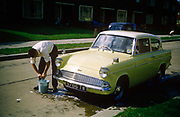 A young man washes the family Ford Anglia car on an Essex estate in the early nineteen sixties. Bending down to wring a leather dry into a bucket the young man cleans his father's beloved Anglia in the street outside the family house which interestingly, is otherwise empty of other cars. This is the new age of car ownership when newfound wealth meant families could afford to buy a vehicle and travel elsewhere after the war years of 1950s austerity. The Ford Anglia is a British car designed and manufactured by Ford in the United Kingdom. The Ford Anglia name was applied to four models of car between 1939 and 1967. 1,594,486 Anglias were produced. The picture was recorded on Kodachrome (Kodak) film in about 1961.
