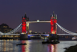 © Licensed to London News Pictures. 23/03/2016. London, UK. Tower Bridge is illuminated in red, one of the colours of the Belgian tricolor flag this evening, in a tribute to victims of the Belgium terrorist attacks which took place yesterday. Landmarks across London are paying tribute this evening. Photo credit : Vickie Flores/LNP