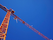 Orange Construction crane on blue sky background as seen from below