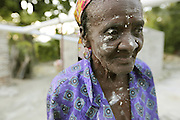 2009/11/16 20:19:00 / haiti 2009 / _MG_2302<br /> PHOTO PETER PEREIRA<br /> <br /> Chrisana Bruny, 84, has her face caked with plaster as she works on patching the wall of her small house on the mountainside above Carrefour, Haiti.