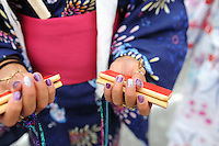 """A young dancer shows some of the specialized rhythm instruments used in the """"bon odori"""" dances at Sunday's 63rd annual Obon Festival at the Buddhist Temple of Salinas."""