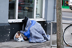 © Licensed to London News Pictures. 14/12/2018. London, UK. A homeless man sleeps on the street outside Barclays Bank in north London. More than 24,000 people in Britain will spend Christmas sleeping rough according to new figures by charity Crisis. Research commissioned by the charity shows that the number of homeless people has risen sharply in England and Wales between 2012 and 2017. It has gone up by 120% in England and 63% in Wales, compared to a fall of 6% in Scotland. With temperatures expected to drop below freezing in the capital, Mayor Sadiq Khan announced that cold-weather shelters would be open citywide. Photo credit: Dinendra Haria/LNP