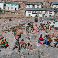 Village farmers who have trekked days from lowland Nepal relax after carrying baskets of their wares to sell at  the Saturday bazar in mountainous Namche Bazaar, leading town of the Sherpa people.