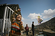 Saboor, 6, at left, and Esan, 13, the eldest son of Noor Agha, at right, fly the kites next to his house inside the cemetery, Kabul, Afghanistan, Saturday, March, 10, 2007. Noor Agha is a renowned kite maker who made kites for the movie makers of the best-selling novel, The Kite Runner, which will be distributed by Dreamworks and Paramount Vantage in Nov. this year. Noor Agha's wives, using their special glue, help him produce enough kites to please the clients' needs. Some of his children can also make their own kites with plastic bags and bamboo sticks. As the Afghan New Year's Day (Nawruz) approaching on March 21, the finger tips of Noor Agha's family got busier for mass production.