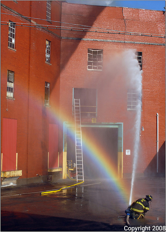 A firefighter keeps a steady stream on the blaze that engulfs the F.X. Matt Brewery on May 29, 2008, in Utica, N.Y., while a rainbow appears to come from the same hose. The fire broke out around 5 p.m. as hundreds were gathering for the annual Saranac Thursday party outside the brewery.
