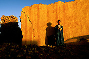 """A boy at dawn with his loaf of bread, Chinguetti, Mauritania , once one of Islam's holiest cities (today it is regarded as the seventh holiest city) it has been dated at a around seven hundred, (700) years old and is famed for it's Koranic libraries and distinctive mosque, Mauritania. From the story """"The Wind and the City""""."""