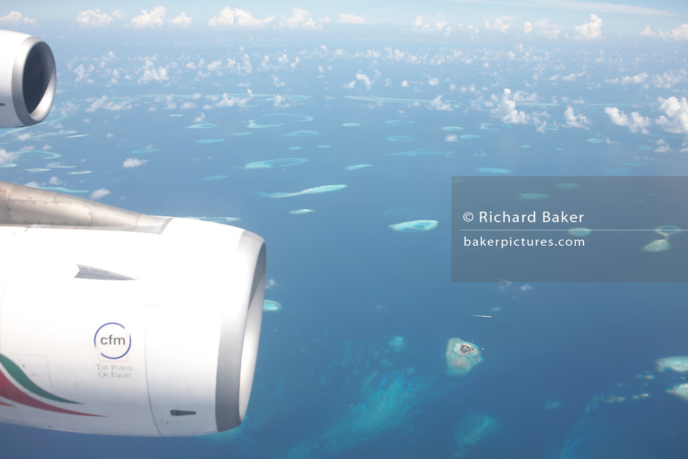 A blue Indian Ocean and remote atolls in the Republic of the Maldives are far below an Airbus port wing and CFM engines.