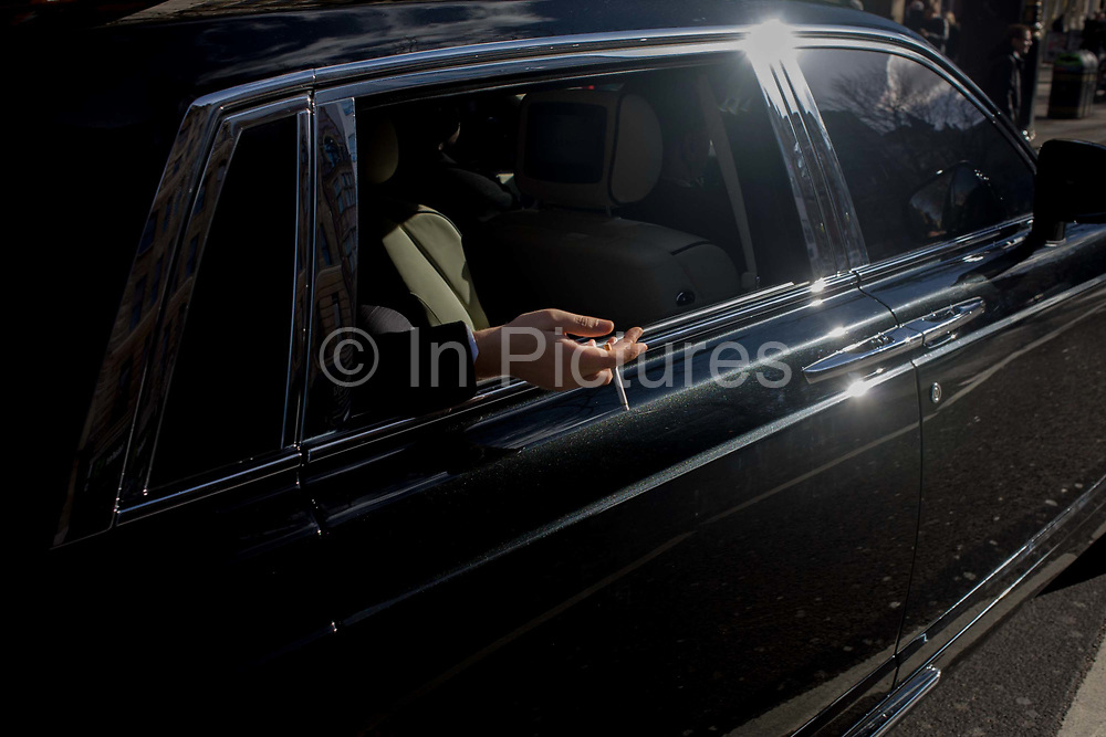 A wealthy man's hand hangs outside his shiny black limousine, holding a cigarette. While stationary in traffic in the capital's West End, the unseen man hangs his arm outside of the very expensive vehicle, polished and shiny in winter sunshine. We see a scene of prosperity and arrogance at a time of an improving economy after years of recession and economic downturn. Here is a person of means and privilege, sat at the back of his Bentley, driven by a chauffeur.