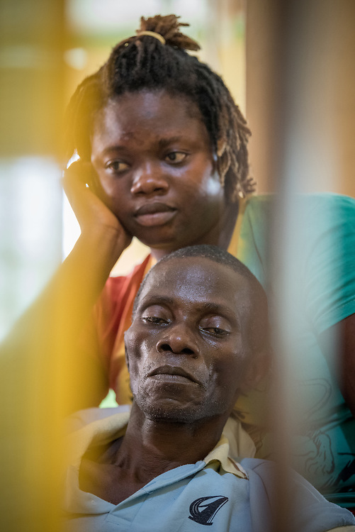 2 November 2019, Ganta, Liberia: Thomas Freeman, a diabetic patient at Ganta Hospital, rests in the arms of his caretaker Maibee Freeman. Located in Nimba county, the Ganta United Methodist Hospital serves tens of thousands of patients each year. It is a founding member of the Christian Health Association of Liberia.