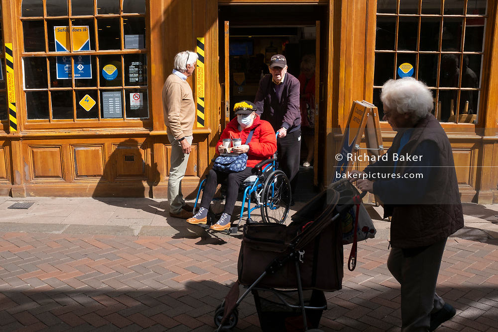 A disabled elderly lady in a wheelchair is pushed  from a branch of Greggs during the Coronavirus pandemic, on 11th July 2020, in Bury St. Edmunds, Suffolk, England.