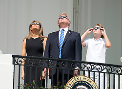 United States President Donald J. Trump, center, accompanied by first lady Melania Trump, left, and Barron Trump, right, look at the partial eclipse of the sun from the Blue Room Balcony of the White House in Washington, DC, USA, on Monday, August 21, 2017. Photo by Ron Sachs/CNP/ABACAPRESS.COM