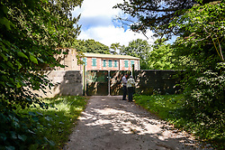 People visit the locked gates of Imber Court in Imber village on Salisbury Plain, Wiltshire, where residents were evicted in 1943 to provide an exercise area for US troops preparing to invade Europe. Roads through the MoD controlled village are now open and will close again on Monday August 22.