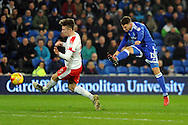 Cardiff City's Anthony Pilkington (r) shoots at goal as Barnsley's Angus MacDonald tries to block. EFL Skybet championship match, Cardiff city v Barnsley at the Cardiff city stadium in Cardiff, South Wales on Saturday 17th December 2016.<br /> pic by Carl Robertson, Andrew Orchard sports photography.