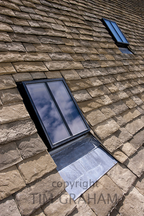 Reproduction Cotswold roof slates and new conservation rooflight window on a Cotswolds stone cottage, Oxfordshire, UK