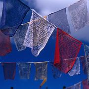 Detail of prayer flag fluttering against blue sky