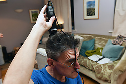 Life in coronavirus lockdown in the UK April 2020. Man having to cut his hair himself using clippers.  Model released.