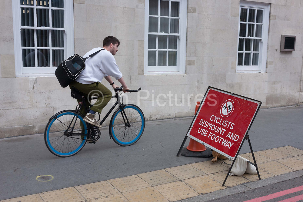 A rider ignores a cyclists dismount sign on the southern side of Londons Tower Bridge, on 6th October 2016, in London, England. Closed for repairs to traffic and disrupting this major Thames crossing and surrounding roads for the next three months.