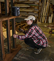Claire Beck paints stairways in the workshop to be used on set for the Rocky Horror Show coming to the Winnipesaukee Playhouse on June.  (Karen Bobotas/for the Laconia Daily Sun)