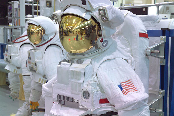 Astronaut space suits displayed in an indoor NASA hangar at Johnson Space Center in Houston, Texas.