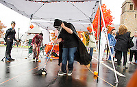"""Gregory DeLuca watches as Anthony DeLuca and Conner Jay play """"Pumpkin Sweep"""" at the Berkshire Hathoway tent during Pumpkin Fest on Saturday afternoon.  (Karen Bobotas/for the Laconia Daily Sun)"""