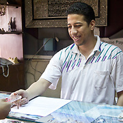 Hotelier at a hostel on Tahrir Square hands a key to a guest. Cairo, Egypt.