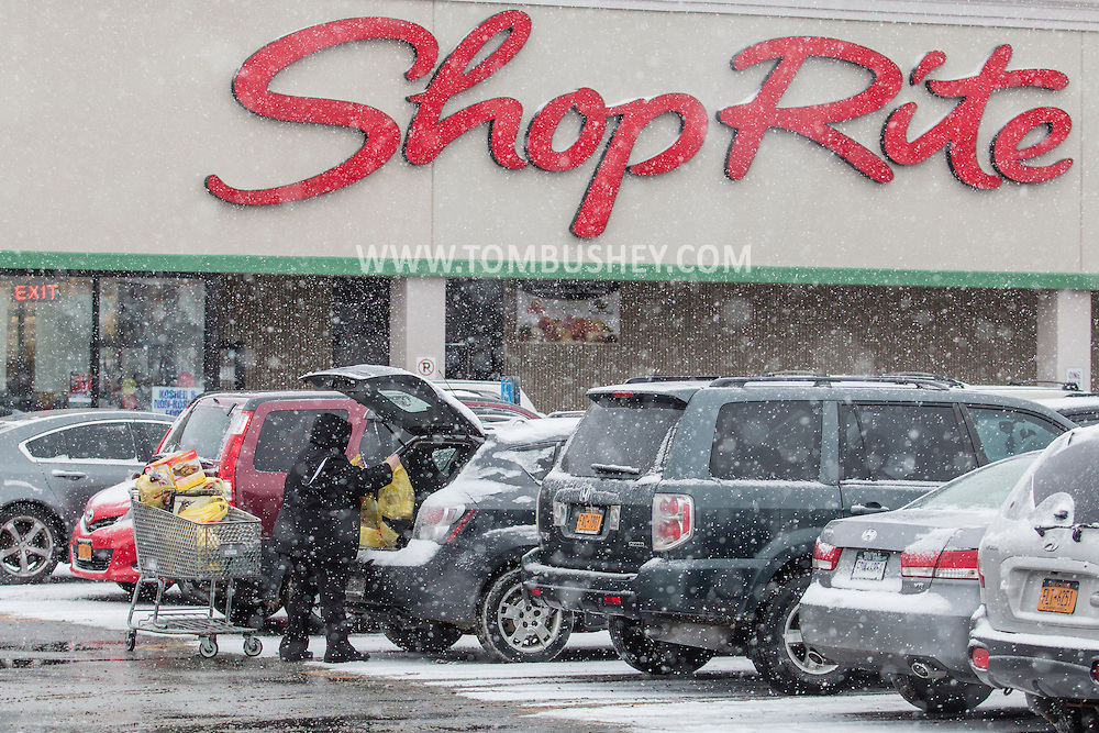 A person loads groceries into a car as snow fallsin the ShopRite parking lot in Middletown, New York. People were buying food in advance of the blizzard forecast to hit Orange County.  The county declared a state of emergency later in the day.
