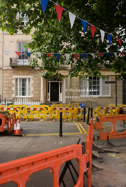Roadworks disruption and patriotic bunting outside a Regency property in Cheltenham, Gloucestershire, England.