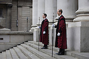 City of London constables stand under the pillars of Royal Exchange, Cornhill before the traditional ceremony of the proclamation of the dissolution of Parliament, on the day that David Cameron announces the beginning of theh 2015 election campaign. City Officers and officials help proclaim the disolving of parliament on the day that the period of Britain's general election starts. Accompanied by constables in cloaks, the three Esquires: The City Marshall, the Sword Bearer and the Mace Bearer (who is properly called 'the Common Cryer and Sergeant-at-arms'); who run the Lord Mayor's official residence, announces from the steps of Royal Exchange, Cornhill, to the capital's ancient financial district.
