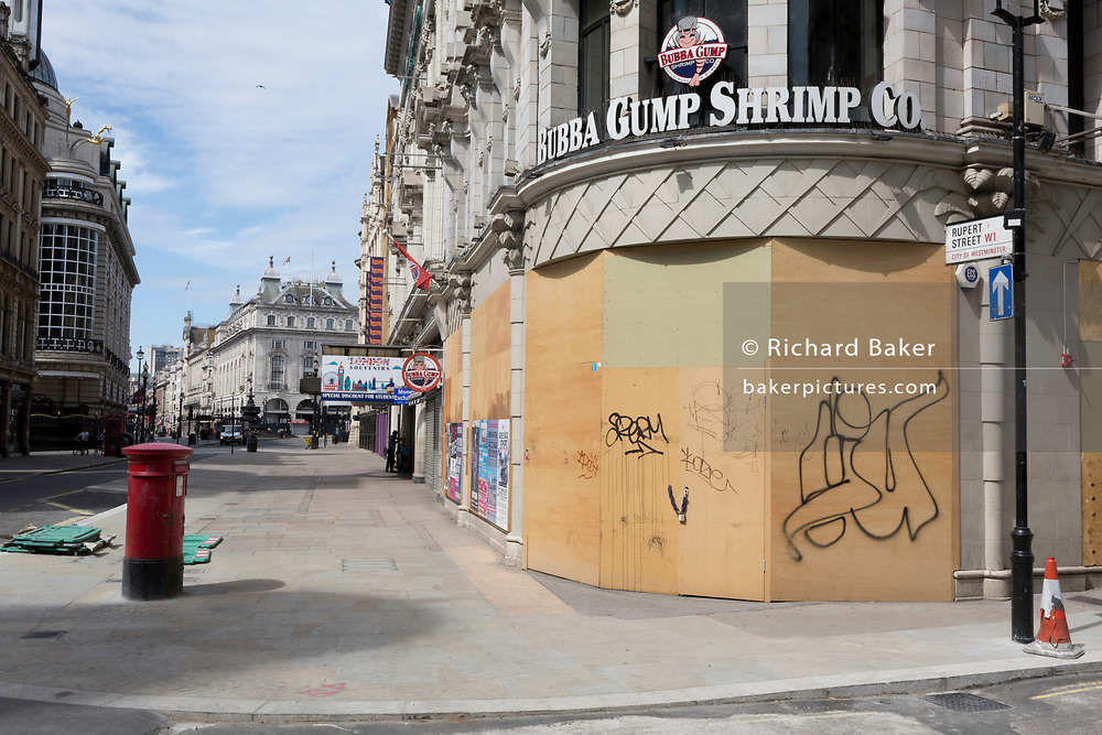 During the UK's Coronavirus pandemic lockdown and on the day when a further 255 deaths occurred, bringing the official covid deaths to 37,048, plyboard wraps a corner shrimp restaurant in Coventry Street near Piccadilly Circus, a closed business in the capital, on 26th May 2020, in London, England.