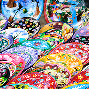 Market stalls selling painted wooden plates and other local souvenirs and handicrafts to tourists visiting Chichen Itza Mayan ruins archeological site in Mexico.