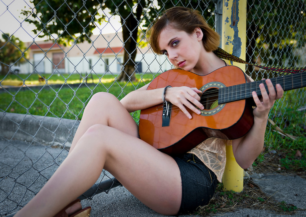 Young woman playing guitar outdoors. Space for copy.