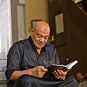 Engrossed in his Qur'an. Rashid, Egypt.