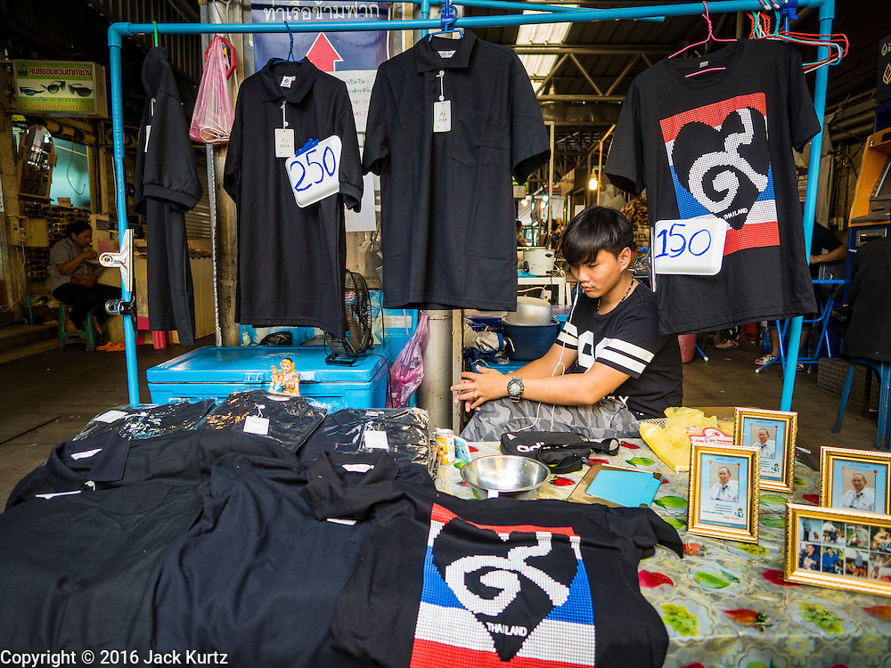 15 OCTOBER 2016 - BANGKOK, THAILAND:  A vendor sells mourning clothes and portraits of Bhumibol Adulyadej, the King of Thailand, near the Grand Palace in Bangkok. King Bhumibol Adulyadej died Oct. 13, 2016. He was 88. His death comes after a period of failing health. With the king's death, the world's longest-reigning monarch is Queen Elizabeth II, who ascended to the British throne in 1952. Bhumibol Adulyadej, was born in Cambridge, MA, on 5 December 1927. He was the ninth monarch of Thailand from the Chakri Dynasty and is known as Rama IX. He became King on June 9, 1946 and served as King of Thailand for 70 years, 126 days. He was, at the time of his death, the world's longest-serving head of state and the longest-reigning monarch in Thai history.     PHOTO BY JACK KURTZ