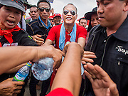 06 APRIL 2014 - BANGKOK, THAILAND:  Red Shirt supporters reach out to pour water on the hands of NATTAWUT SAIKUA, a Red Shirt core leader, as he walks through the crowd at a Red Shirt rally in a Bangkok suburb Sunday. Red Shirts and supporters of the government of Yingluck Shinawatra, the Prime Minister of Thailand, gathered in a suburb of Bangkok this weekend to show support for the government. The Thai government is dealing with ongoing protests led by anti-government activists. Legal challenges filed by critics of the government could bring the government down as soon as the end of April. The Red Shirt rally this weekend was to show support for the government, which public opinion polls show still has the support of most of the electorate.  PHOTO BY JACK KURTZ