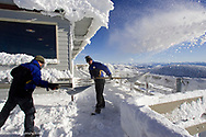 Workers Shovel Snow From Summit House Deck at Whitefish Mountain Resort in Montana