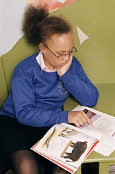 Primary school girl reading a book,