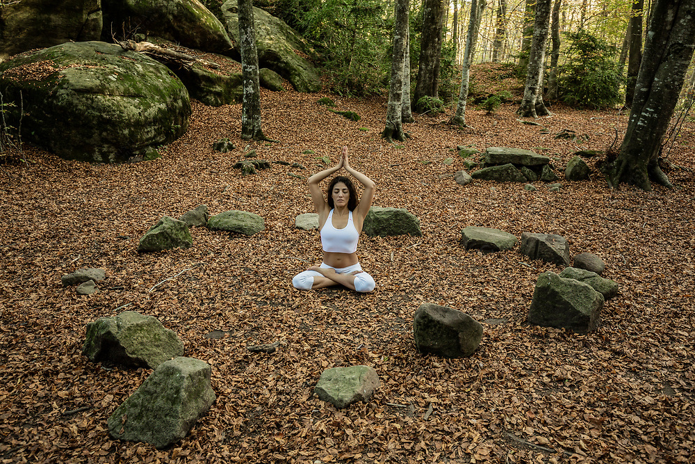 Woman meditating inside stone circle in forest