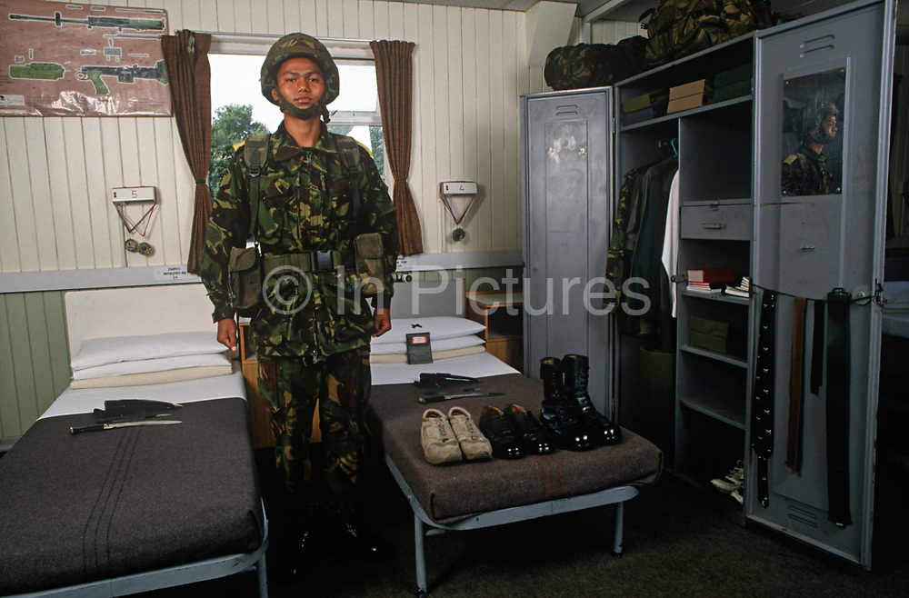 A British Army Gurkha recruit stands to attention during a barracks inspection at the Gurkha Regiments training centre at Church Crookham, on 16th January 1996, in England UK. Some 60,000 young Nepalese boys aged between 17 - 22 or 25 for those educated enough to become clerks or communications specialists report to designated recruiting stations in Nepals Himalayan foothills each November, most living from altitudes ranging from 4,000 - 12,000 feet. Only 160 are recruited with training continuing at this barracks until joining various units within the army. The Gurkhas training wing in Nepal has been supplying youth for the British army since the Indian Mutiny of 1857.