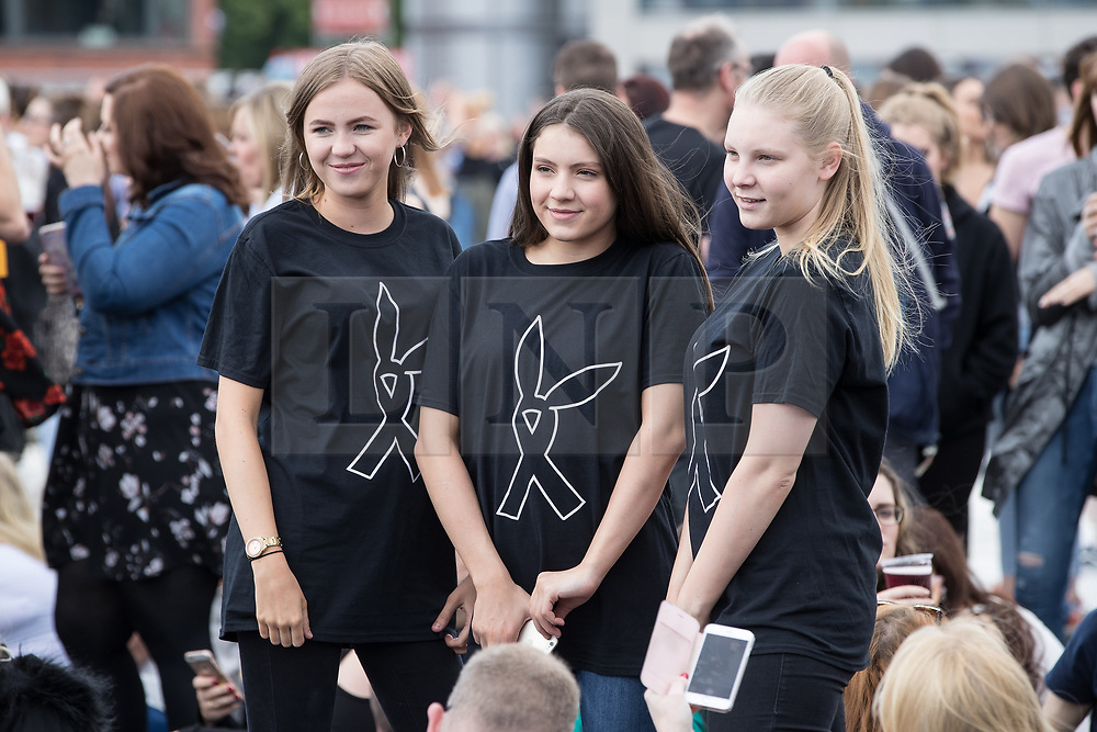 © Licensed to London News Pictures . 04/06/2017 . Manchester , UK . Three girls wearing t-shirts with the One Love Manchester symbol on their t-shirts as the crowd gathers in front of the stage . The One Love Manchester benefit concert for victims of the Manchester Arena terrorist attack , at the Emirates Old Trafford Cricket Stadium . Ariana Grande, Justin Bieber, Coldplay, Katy Perry, Miley Cyrus, Pharrell Williams, Usher, Take That, Robbie Williams, Black Eyed Peas and Niall Horan are amongst the performers . Photo credit : Joel Goodman/LNP