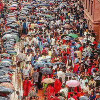 A crowd shelters under umbrellas as Hindu celebrants gather amongst pagodas to celebrate Krishna's birthday at the temple square in Patan Nepal, 1996.