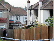 © Licensed to London News Pictures. 23/09/2011. LONDON, UK. A police man stands at the rear of the property. The upper floor and roof of the property were destroyed. Six people, including three children, two teenagers and an adult have died following a house fire in Neasden, North West London today (24 Sept 2011). Emergency services were called tot he blaze in the early hours of the morning. Photo credit:  Stephen Simpson/LNP