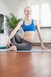 Young woman doing twisted yoga on exercise mat in living room, Bavaria, Germany