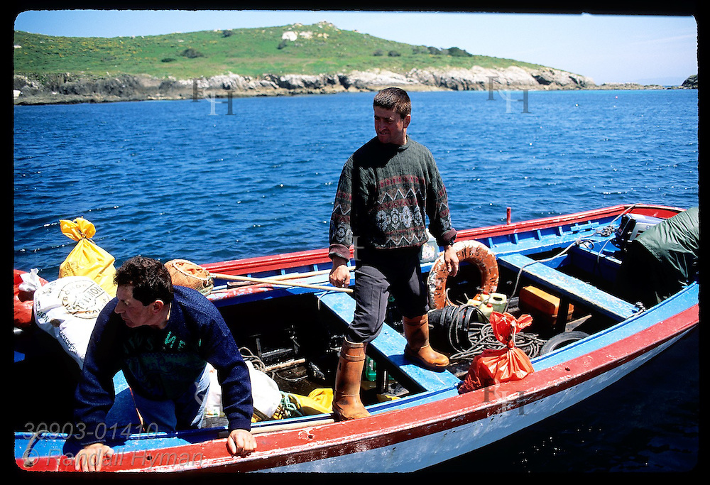 Fishermen on boat head home from day of harvesting goose barnacles on Sisargas Islands; Galicia, Spain.
