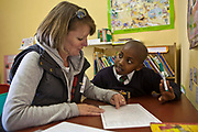 A female teacher guides a young school-boy though a reading exercise in the reading corner in a class room in Zonnebloem School, Cape Town, South Africa.  The volunteer teacher has been provided to the school by Shine Centre which is a charity that aims to address the high illiteracy rate in South Africa by improving literacy levels among children in schools and disadvantaged communities.