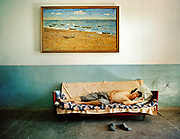 Esbolov Saylau (Karakalpak man), owner of the only hotel in  Moynaq, now adandoned. Sits under a painting of the Sea in the late 70's.<br /> <br /> In Moynaq town, former fishing port on the Aral Sea, now 180km from shore. <br /> Since 1960's, The Aral Sea has been drained of 75% of its water, because of the diversion of upstream rivers that are used for cotton plantation. It use to be the 4th largest lake in the world. The resulting desertification is accelerating dramatically global warming. High salinity means no more fish. Anthrax and rabbies test were also done in a former island in the sea that is now linked to the shore.... <br /> Uzbekistan.