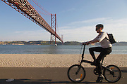 People exercising by Tagus riverside in Lisbon, with Cristo-Rei (King Christ) monument and 25th of April bridge in the background.