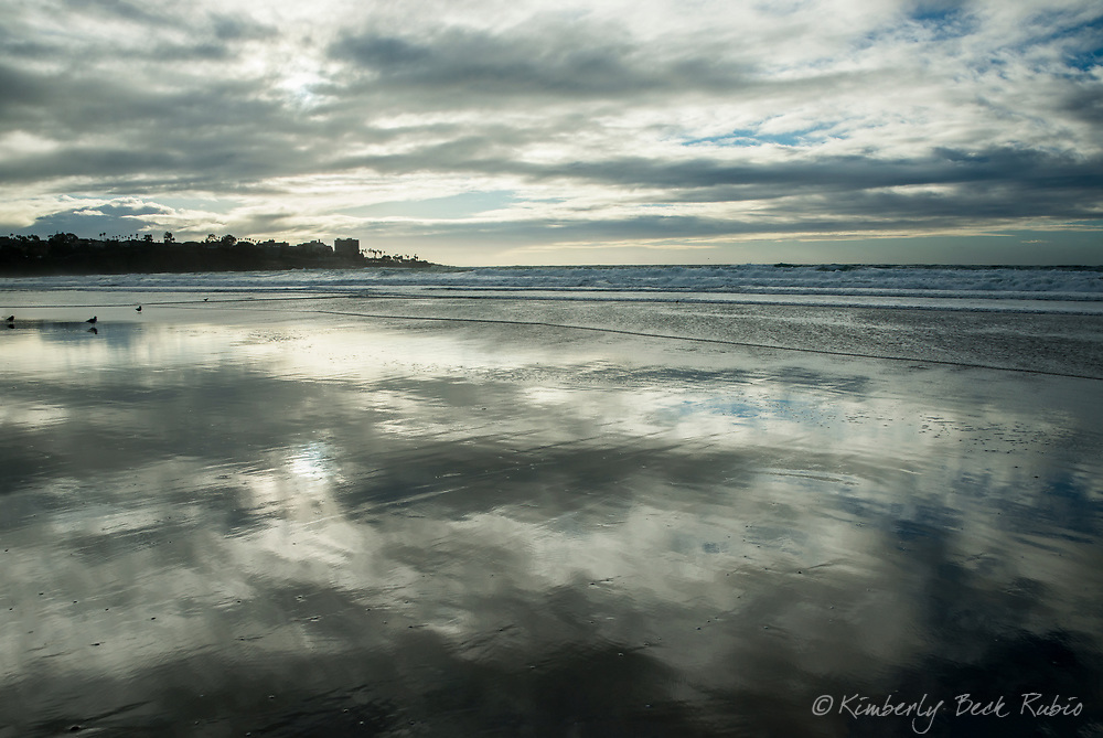 Clouds reflecting on wet sand at La Jolla Shores beach in La Jolla, California, on a rare stormy day in winter.