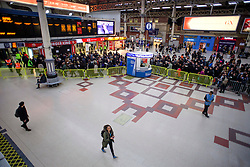 © Licensed to London News Pictures. 14/12/2016. London, UK. People walk through a mainly empty station as other passengers queue for a restricted Gatwick Express service (background) at rush hour at Victoria Station on 14 December 2016, as hundreds of thousands of rail passengers face a second day of a 3 day all-out strike in an escalating dispute over the role of conductors between Southern Rail and the RMT Union. Photo credit: Ben Cawthra/LNP