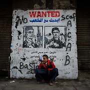 A child seats near a anti military rule graffiti in central Cairo.